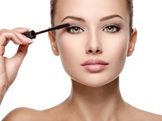 woman applying cosmetic mascara on eyelashes using curling brush