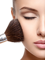 woman  applying dry cosmetic powder on the face