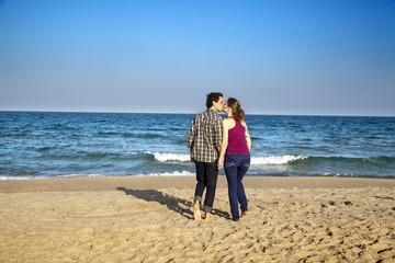 Pareja de enamorados besándose en la playa