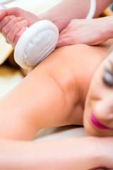 Frau bekommt Rückenmassage im Wellness Spa