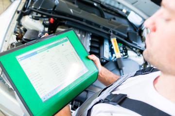 Automechaniker mit Diagnosegerät in Autowerkstatt