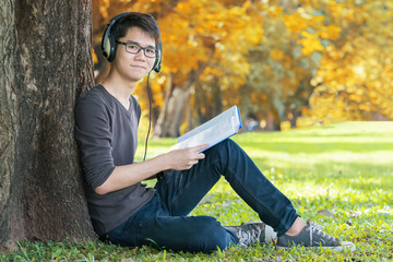 Handsome student listening music in the park