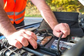 Autofahrer in Warnweste check seine Autobatterie