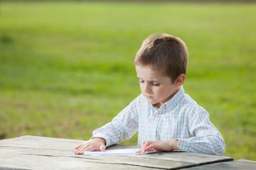 boy making paper plane