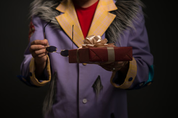 Unrecognizable Clown man with Christmas gift box