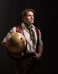 Mature man in costume of traveler holding old globe