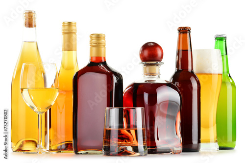 Bottles and glasses of assorted alcoholic beverages over white - 73270802