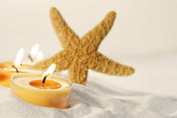 Tea light candles in sand with star fish