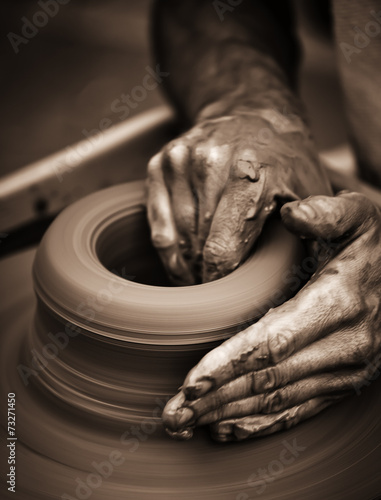 Hands working on pottery wheel - 73271450