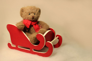 Teddy Bear Sitting in a Little Red Sled