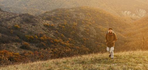 Hiker man walking in autumn mountains