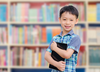 Asian boy with tablet computer in school library smiling at came