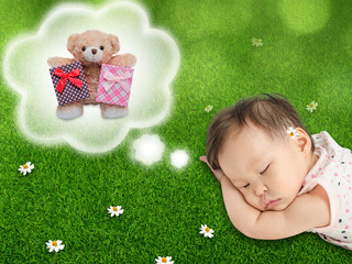 Little baby girl sleeping and dreaming on grass field.