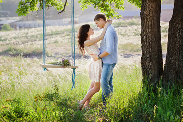Young kissing couple under big tree with swing