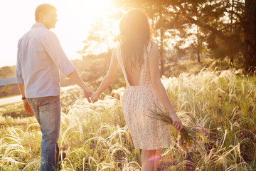 lovers walking in a field at sunset holding hands