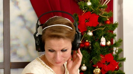 Beautiful adult woman listening music against Christmas tree
