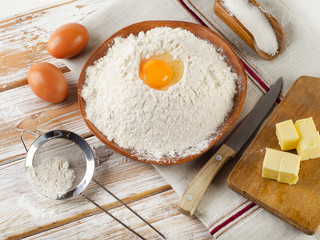 Eggs, flour, sugar, butter on  white  wooden background