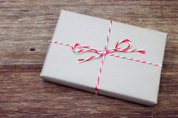 brown paper parcel tied with red and white string on wood table