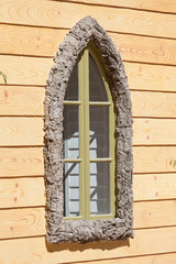 Decorative window in a frame from a pith tree on a wooden wall