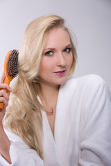 Frau bürstet sich das blonde Haar