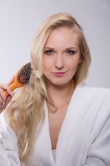 Hübsche junge Frau bürstet sich das blonde Haar