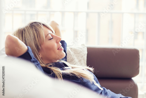 Relaxed young woman lying on couch poster