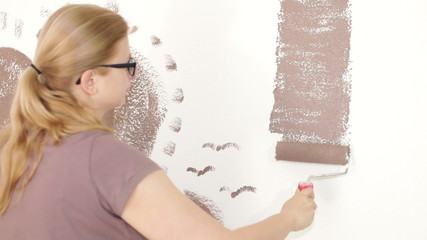 Woman with paint roller painting wall