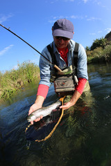 Fly fisherman holding recently caught fish