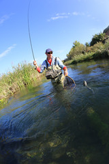 Fly fisherman catching rainbow fish