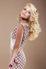 Graceful Woman in Retro Polka Dot Dress Looking Back