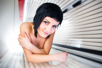 Pretty, young woman tanning her skin in a modern sunbed