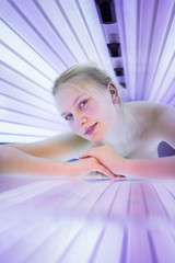 Pretty, young woman tanning her skin in a modern solarium