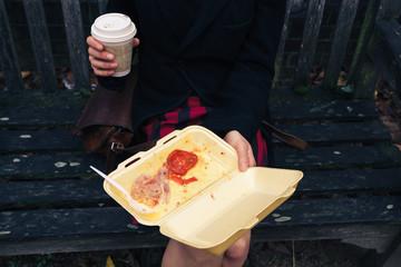 Woman having breakfast on bench