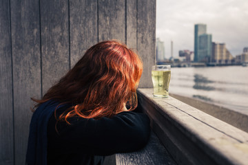 Woman drinking beer by the river