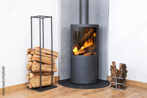 Modern burning stove next to a wood logs rack - 73285201