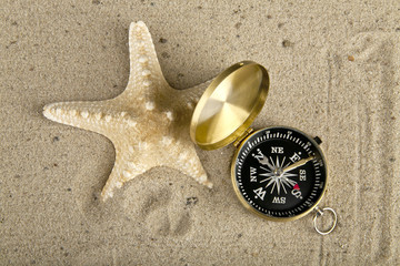 starfishes  and compass on sand