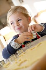 Cheerful little girl baking cookies