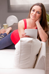 woman on a couch enjoying content on a tablet