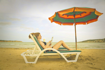 Girl using a tablet at the beach
