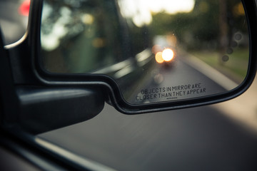 Side rear view mirror of a car on a road