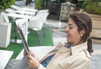 Brunette woman reading the newspaper