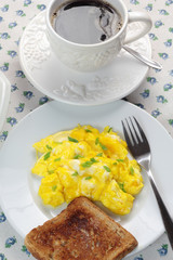 Scrambled eggs, toast and cup of coffee.