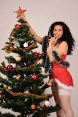 Girl that adorns the Christmas tree, in Santa red costume