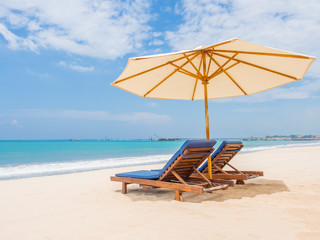 Relaxing couch chairs with parasol on white sandy Beach