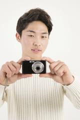 Asian young man taking photo by digital camera