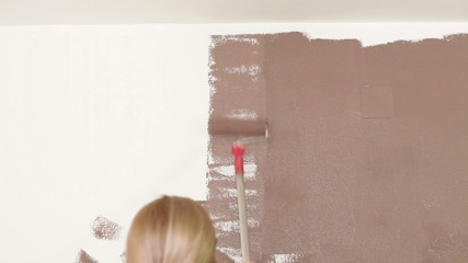 Woman with paint roller painting interior