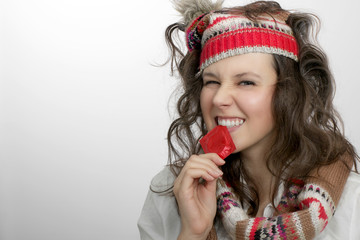Girl with knitted hat and scarf  holding with teeth a red condom