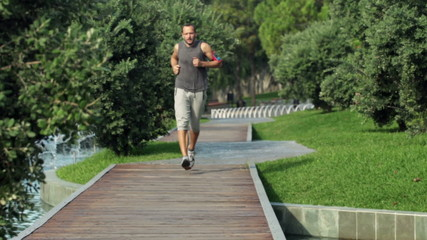 Young, attractive man jogging in city park
