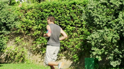 Young, attractive man jogging in city park slow motion, shot at