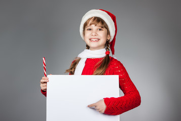 happy girl in santa claus hat holding a poster